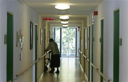 A elderly woman walks along a corridor in a file photo. REUTERS/Michaela Rehle