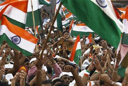 Supporters of veteran Indian social activist Anna Hazare shout slogans as they wave Indian national flags on the seventh day of Hazare's fast at Ramlila grounds in New Delhi August 22, 2011. REUTERS/Adnan Abidi