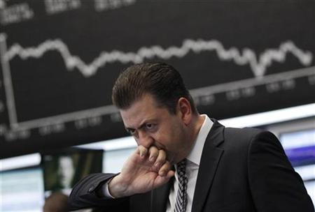 A trader reacts at his desk in front of the DAX board at the Frankfurt stock exchange August 18, 2011. REUTERS/Alex Domanski