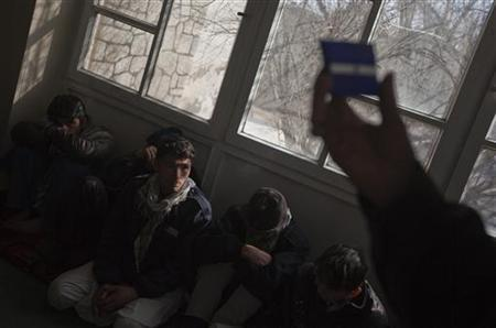 A worker from Medicins Du Monde clinic holds a condom as he gives information to drug addicts in Kabul February 8, 2011. REUTERS/Ahmad Masood