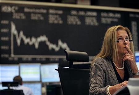 A share trader checks share prices as she sits behind her trading terminals at the trading floor of the German stock exchange in Frankfurt, October 20, 2008. REUTERS/Kai Pfaffenbach