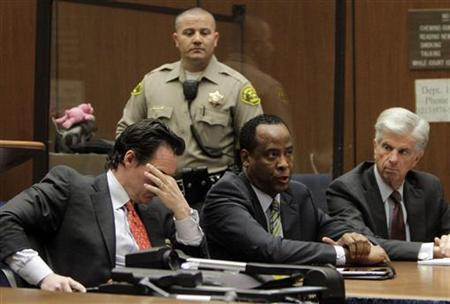 Doctor Conrad Murray (C), the late Michael Jackson's personal physician, sits with his lawyers Edward Chernoff (L) and Michael Flanagan during his arraignment on a charge of involuntary manslaughter in the pop star's death, in Los Angeles, California, January 25, 2011. REUTERS/Pool/Irfan Khan
