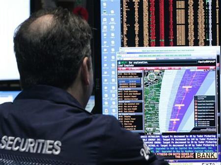 A trader looks at the path of Hurrican Irene on the floor of the New York Stock Exchange August 26, 2011. REUTERS/Brendan McDermid