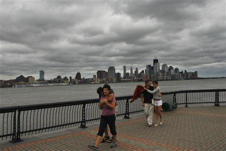 With the skyline of New York behind them, people walk along Hudson river after the pass of Hurricane Irene at Hoboken in New Jersey August 28, 2011. REUTERS/Eduardo Munoz