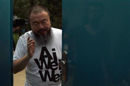 Dissident Chinese artist Ai Weiwei closes the door to his studio after speaking to the media in Beijing June 23, 2011. REUTERS/David Gray