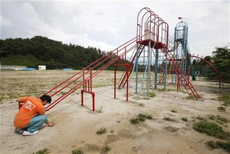 A worker of an office cleaning company monitors the level of radiation at a playground of an elementary school in Fukushima, northern Japan August 6, 2011. REUTERS/Yuriko Nakao