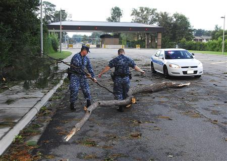 Sailors assigned to the base police department move debris from Hurricane Irene at one of the entrances to Joint Expeditionary Base Little Creek-Fort Story in Virginia Beach, VA, in this photo taken and released on August 28, 2011. REUTERS/Spencer R. Layne/U.S. Navy/Handout