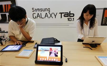 People test out Samsung Electronics' new tablet 'Galaxy Tab 10.1' during its launch ceremony at the company's headquarters in Seoul in this July 20, 2011 file photo. REUTERS/Jo Yong-Hak
