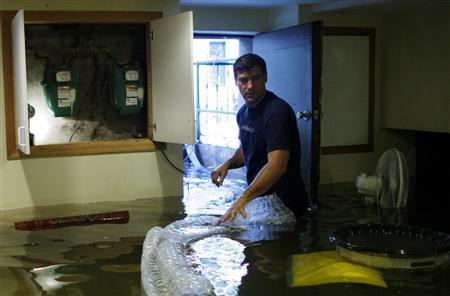 American-Russian Andre Kozlov, 38, walks through his flooded basement after the pass of Hurricane Irene at Hoboken in New Jersey August 28, 2011. REUTERS/Eduardo Munoz