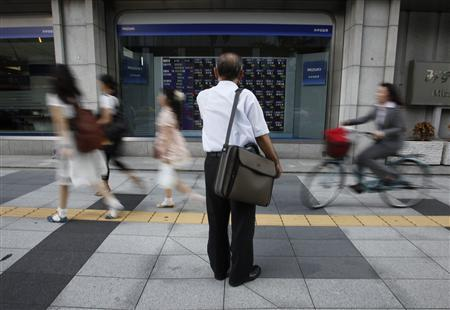 A man looks at a stock quotation board outside a brokerage in Tokyo, August 30, 2011. REUTERS/Toru Hanai