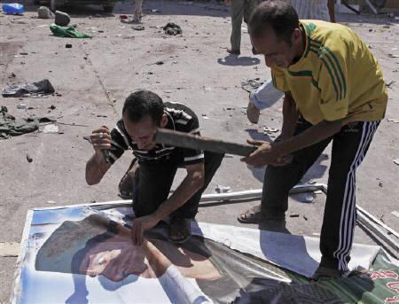 A man tears a poster of Muammar Gaddafi in Abu Salim district  in Tripoli August 26, 2011. REUTERS/Youssef Boudlal/Files