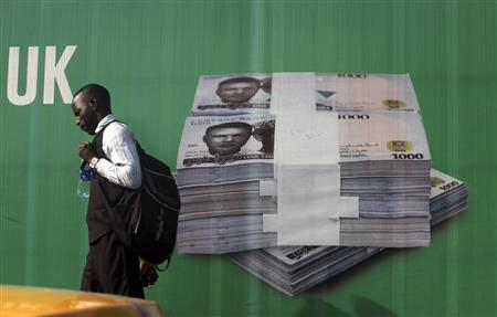 A man walks past a promotional banner showing a photograph of a pile of Nigerian naira along a road in Lagos, November 24, 2010. REUTERS/Akintunde Akinleye