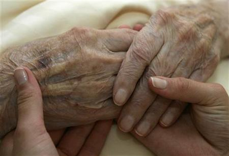 A young carer holds the hands of an elderly woman in a residential home for the elderly in Planegg near Munich June 19, 2007. REUTERS/Michaela Rehle