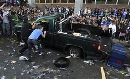<p>Vancouver Canucks fans flip over a pickup truck in downtown Vancouver, British Columbia during rioting after the Canucks lost Game-7, the final and deciding game of the Stanley Cup playoffs to the Boston Bruins, June 15, 2011. REUTERS/Anthony Bolante</p>