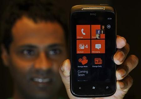 An employee poses with a mobile phone with the new Windows 7 operating system after its arrival in British shops, in central London October 21, 2010. REUTERS/Toby Melville