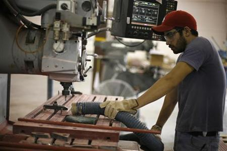 A Mexican worker uses a saw to shape fiberglass at a factory near the border with Texas, October 29, 2009. REUTERS/Tomas Bravo