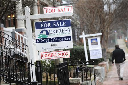 A man walks past signs marking houses for sale in Washington, in this January 24, 2010 file photo. REUTERS/Jonathan Ernst/File