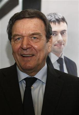 Former German chancellor Gerhard Schroeder stands in front of a picture of Nils Schmid, Social Democratic Party (SPD) top candidate for the Baden-Wuerttemberg state election before an election campaign in Stuttgart March 17, 2011. The Baden-Wuerttemberg state election is due to take place on March 27, 2011. REUTERS/Michaela Rehle