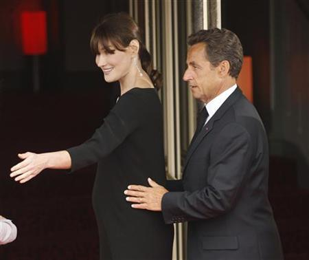 French President Nicolas Sarkozy puts his hands upon his pregnant wife Carla Bruni-Sarkozy as they greet leaders for dinner at the G8 Summit in Deauville May 26, 2011. REUTERS/Kevin Lamarque