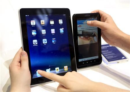 File photo of people comparing the performance of Apple's iPad (L) and Samsung's Galaxy Tab tablet devices at the Internationale Funkausstellung (IFA) consumer electronics fair at ''Messe Berlin'' exhibition centre in Berlin, September 2, 2010. Samsung Electronics Co has said September 5, 2011, it will stop promoting its new tablet computer at Europe's biggest consumer electronics fair after a court-ordered sales injunction in Germany, the latest setback in its global patent battle with Apple Inc. A Dusseldorf court ordered the South Korean company to stop selling Galaxy Tab 7.7 on Friday when the annual IFA electronics show started in Berlin. The Galaxy Tab 7.7 is not on sale yet but we've decided to respect the court order,'' Samsung spokesman James Chung said. Samsung and Apple have been locked in acrimonious battle over smartphones and tablets patents since April as Apple seeks to rein in the growth of Google's Android phones by taking directly aim at the biggest Android vendor, Samsung. REUTERS/Thomas Peter/Files