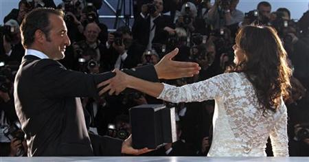 Actor Jean Dujardin (L) poses with cast member Berenice Bejo during a photocall after receiving the Best Actor award for his role in director Michel Hazanavicius' film ''The Artist'' during the closing ceremony of the 64th Cannes Film Festival May 22, 2011. REUTERS/Jean-Paul Pelissier