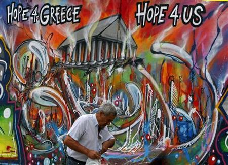 A man walks past a graffiti depicting the economic situation in Europe, in Lisbon August 22, 2011. REUTERS/Hugo Correia