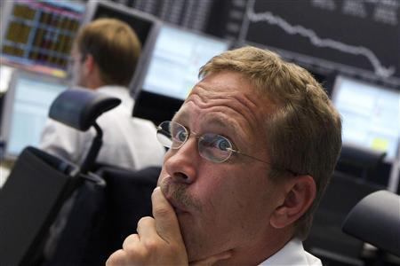 A trader reacts at his desk in front of the DAX board at the Frankfurt stock exchange September 5, 2011. REUTERS/Alex Domanski