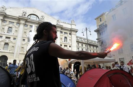 A demonstrator holds a flare in front of Milan's Stock Exchange Palace, September 6, 2011. REUTERS/Paolo Bona