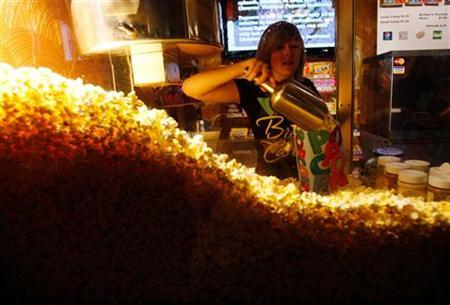 Cailynn Williams, 17, fills a bag of popcorn for a customer at the New Strand Theater in West Liberty, Iowa July 8, 2011. REUTERS/Jessica Rinaldi