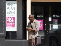 <p>A man checks his mobile phone as he walks past a T-Mobile store in downtown Los Angeles, August 31, 2011. REUTERS/Fred Prouser</p>
