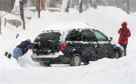 A man helps push his neighbor's car up a hill after more than twelve inches of snow fell in Minneapolis, February 21, 2011. REUTERS/Eric Miller