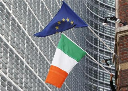 A man adjusts an Irish flag as it flies next to a European Union flag near the EU Commission headquarters in Brussels October 2, 2009. REUTERS/Francois Lenoir