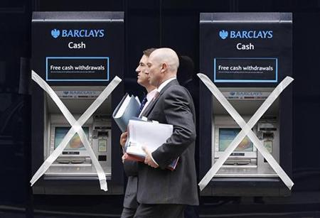 Two men pass a pair of closed cashpoints marked with masking tape, outside a Barclays Bank branch being refurbished in the financial district City of London August 31, 2011. REUTERS/Chris Helgren