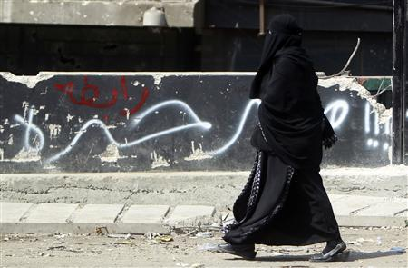 An Egyptian veiled woman walk past a wall that reads ''Egypt's Free'', built around a building housing the embassy at the site of clashes between protesters and riot police in Cairo September 10, 2011. Israel flew its ambassador home from REUTERS/Amr Abdallah Dalsh