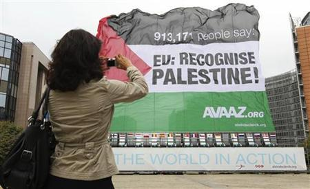 A woman takes a picture of a giant Palestinian flag displayed outside the European Commission headquarters in Brussels September 12, 2011. REUTERS/Thierry Roge