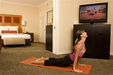 <p>A woman practices yoga in Kimpton's Hotel Palomar in San Francisco, California in this June 2004 handout. Hotel chains are delivering everything from yoga videos to recumbent bicycles to guests who prefer to work out their jet lag, or shape up for that business meeting, in the privacy of their rooms. REUTERS/Karna Kurata, Kimpton Hotels and Restaurants/Handout</p>