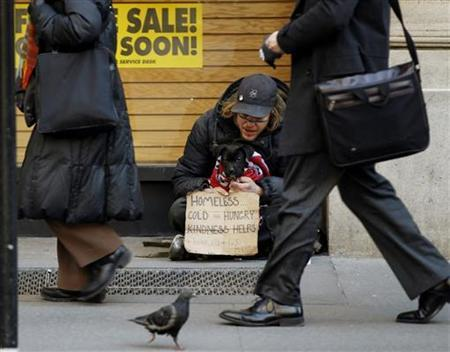 Pedestrians walk past a man as he panhandles for money while sitting with a puppy on a sidewalk in the financial district of New York March 3, 2011. REUTERS/Lucas Jackson
