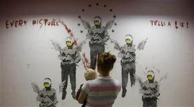 "<p>Visitors look at the work ""Every Picture Tells A Lie"" by street artist Banksy at the Kuenstlerhaus Bethanien in Berlin, September 13, 2011. REUTERS/Tobias Schwarz</p>"