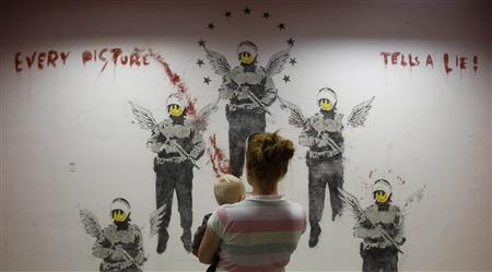 Visitors look at the work ''Every Picture Tells A Lie'' by street artist Banksy at the Kuenstlerhaus Bethanien in Berlin, September 13, 2011. REUTERS/Tobias Schwarz