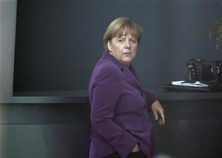 German Chancellor Angela Merkel is seen through a window of the Chancellery as she waits for the arrival of Finnish Prime Minister Jyrki Katainen (not pictured) in Berlin, September 13, 2011. REUTERS/Thomas Peter