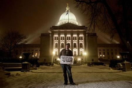 Benjamin Frelka of Madison, Wisconsin poses for a portrait with his sign as he marches around the Capitol while protesters gather to protest against a proposed bill by Governor Scott Walker in Madison, Wisconsin February 21, 2011. REUTERS/Darren Hauck