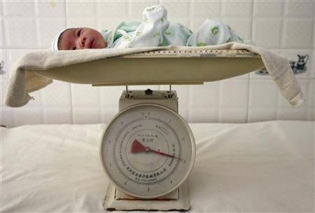 A newborn baby is put on a weight at a hospital in Suining, southwest China's Sichuan province September 14, 2007. REUTERS/Stringer