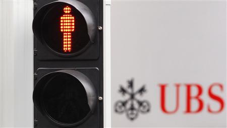 A traffic sign is seen next to an UBS bank logo in Zurich in this July 14, 2011 file photo. REUTERS/Christian Hartmann/files