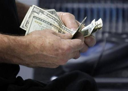A customer counts his cash at the register while purchasing an item at a Best Buy store in Flushing, New York March 27, 2010. REUTERS/Jessica Rinaldi