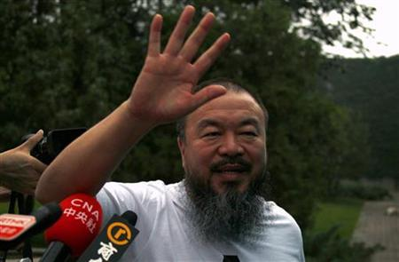 Dissident Chinese artist Ai Weiwei waves from the doorway of his studio after he was released on bail in Beijing June 23, 2011. REUTERS/David Gray