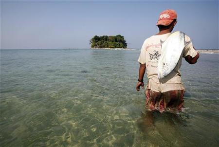 A fisherman carries a fish near Chitthu Island at Ngwesaung Beach February 14, 2010. REUTERS/Soe Zeya Tun