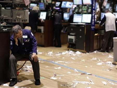 A trader sits down, on the floor of the New York Stock Exchange August 18, 2011. REUTERS/Brendan McDermid