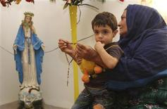 <p>An Iraqi Christian refugee woman with a child on her lap holds a rosary as she prays in front of a statue of the Virgin Mary at her house in Arbil, about 300 km (190 miles) north of Baghdad, September 11, 2011. REUTERS/Azad Lashkari</p>