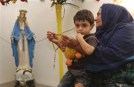 An Iraqi Christian refugee woman with a child on her lap holds a rosary as she prays in front of a statue of the Virgin Mary at her house in Arbil, about 300 km (190 miles) north of Baghdad, September 11, 2011. REUTERS/Azad Lashkari