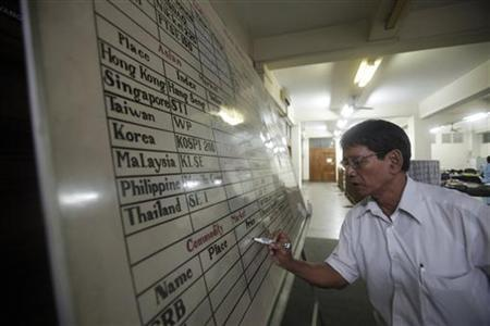An office staff writes on a white board at the Myanmar Securities Exchange Centre (MSEC) in Yangon September 16, 2011. REUTERS/Soe Zeya Tun